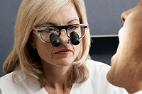 Female dentist wearing surgical loupes, examining patient, close-up