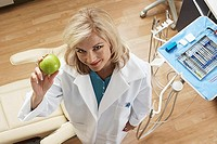 Female dentist holding green apple in dental surgery, smiling, portrait, overhead view