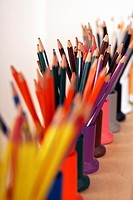 Row of multi-coloured colouring pencils in pots, close-up still life, differential focus