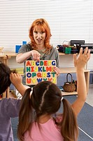 Children 4-6 learning the alphabet in classroom, hands raised, focus on teacher in background