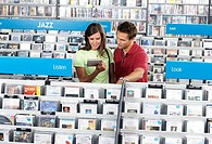 Young couple shopping for jazz CDs in record shop, standing in aisle behind rack, smiling (thumbnail)