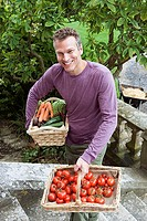 Man carrying baskets of tomatoes and vegetables up garden steps, smiling, portrait, elevated view