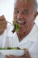 Senior man eating fresh salad, close-up, smiling, portrait