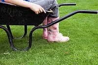 Girl 9-11 in pink wellington boots sitting in wheelbarrow in field, side view, low section