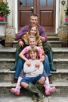 Two generation family sitting in line on steps in front of house, smiling, front view, portrait