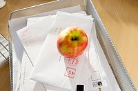 Apple and post in in-tray on office desk, close-up, elevated view still life