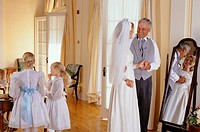 Father talking to bride indoors, flower girls 4-7 in background