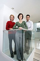 Three business colleagues standing beside glass partition in office, smiling, portrait