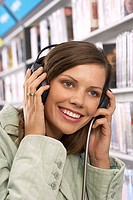 Young woman wearing headphones, listening to CDs in record shop, smiling, close-up