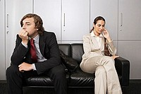 Anxious businessman and businesswoman sitting on sofa in office reception area, waiting patiently