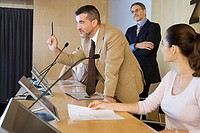 Businessman talking in conference room, gesturing, colleagues listening, side view