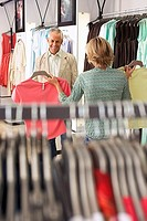 Mature couple shopping in clothes shop, woman showing two different coloured tops to husband, man smiling, focus on background