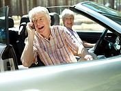 Senior couple sitting in convertible car, man using mobile phone, smiling, side view