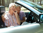 Senior couple sitting in convertible car, using mobile phone, smiling, side view
