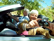 Senior couple driving in convertible car along country road, woman taking photograph, side view