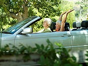 Senior couple driving in convertible car along country road, woman with arms up, smiling, side view