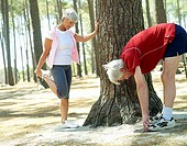 Active senior couple in sportswear stretching legs, woman leaning against tree, man touching toes