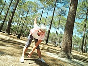 Active senior woman in sportswear exercising in wood, stretching, touching toes, smiling tilt