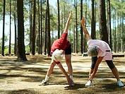 Active senior couple in sportswear exercising in wood, stretching, touching toes, front view