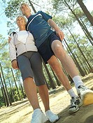Senior couple in sportswear standing in clearing in wood, smiling, low angle view tilt