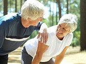 Senior couple in sportswear taking break from jogging, leaning on knees, smiling, side view