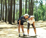 Senior couple in sportswear taking break from jogging, leaning on knees, smiling