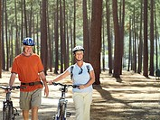 Senior couple in cycling helmets walking through wood with bicycles, side by side, front view