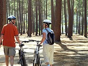 Senior couple in cycling helmets walking through wood with bicycles, side by side, rear view