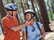 Senior couple standing in wood, man adjusting strap on woman's cycling helmet, smiling tilt
