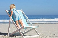 Girl 2-4 standing on deckchair on sandy beach, rear view, sea in background