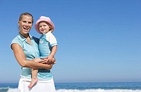 Mother and daughter 2-4 standing on beach, girl in woman's arms, smiling, portrait