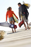 Young couple carrying surfboards along boardwalk on beach, rear view, surface level tilt