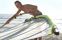 Young woman in bikini assembling windsurfer on sandy beach, smiling, side view, portrait