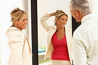 Woman trying on new clothes in fitting room, hand in hair, reflection in mirror, husband looking on