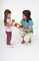 Young woman offering a girl an apple from a plate