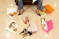Woman trying on different pairs of high heels in shoe shop, low section, elevated view