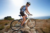 Female mountain biker cycling across extreme terrain in bright sunlight, sea in background