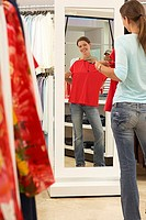 Woman trying on red top in clothes shop, looking at reflection in mirror, smiling, rear view