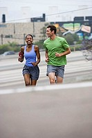 Couple jogging up sloping street, woman listening to MP3 player strapped to arm, smiling