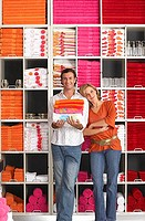 Couple shopping in department store, woman leaning against boyfriend, man holding pile of folded towels, smiling, front view, portrait, shelves in bac...