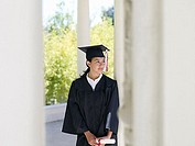 University student in graduation gown and mortar board holding diploma, smiling