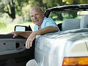 Senior man sitting in driver's seat of convertible car, smiling, portrait