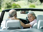 Senior couple sitting in convertible car, woman looking over shoulder, smiling, rear view, portrait