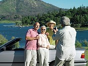 Two senior couples standing beside convertible car near lake, smiling, man filming with camcorder