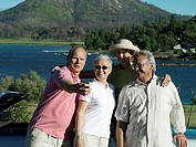 Two senior couples standing beside car near lake, man taking photograph with digital camera, smiling