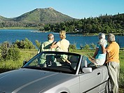 Two senior couples standing beside convertible car, admiring view of lake, rear view