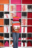 Woman shopping in department store, holding large pile of towels beside shelf, face obscured