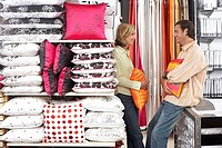 Couple shopping for cushions in department store, standing face to face, smiling, side view