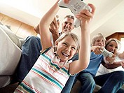 Family sitting on sofa at home, playing with video games console, smiling, low angle view tilt
