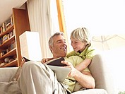 Father and son 6-8 relaxing on sofa at home, man reading book, smiling, low angle view tilt